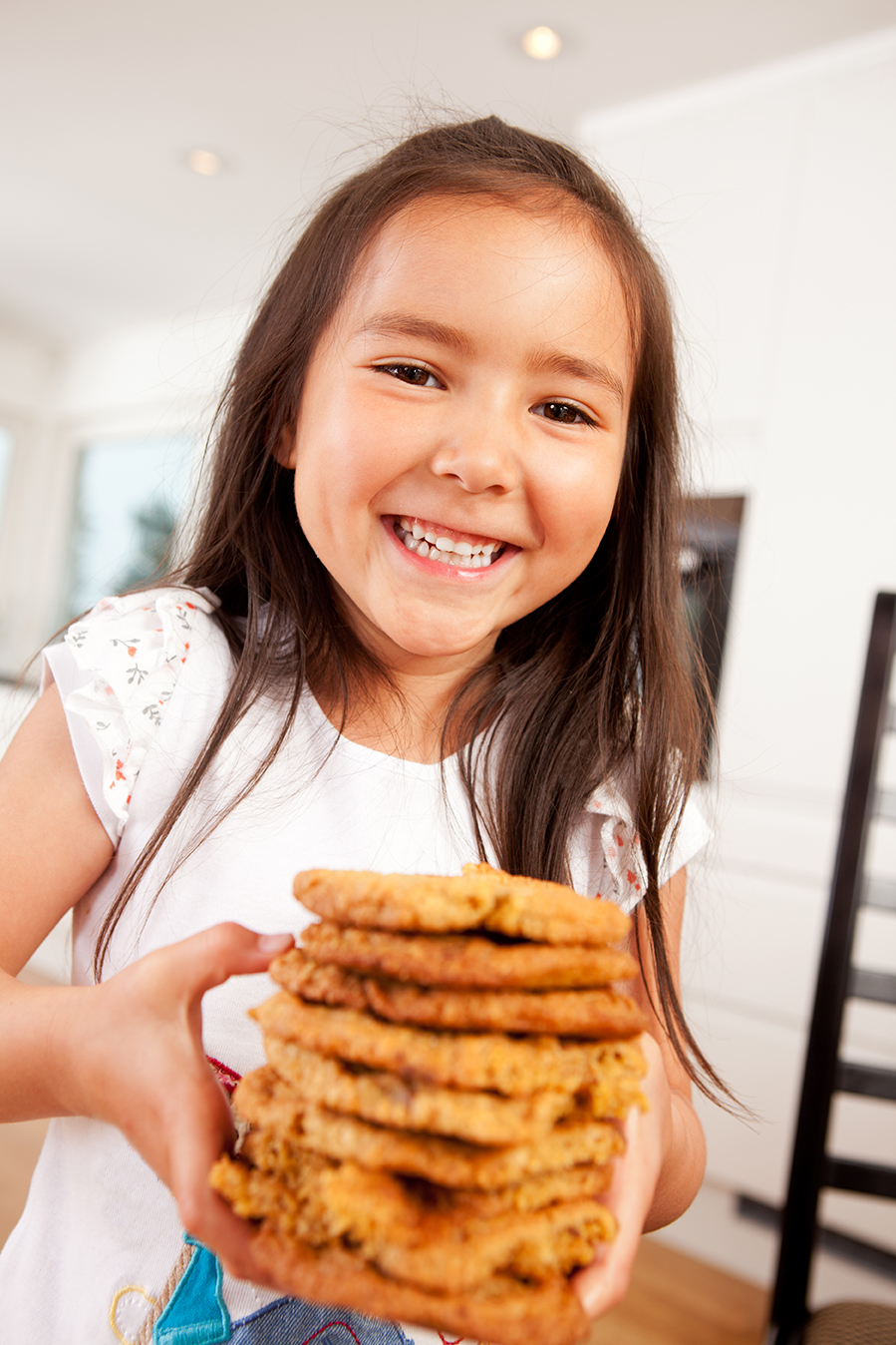 Happy, laughing and smiling young cute girl holding stack of lar