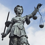 Statue of Justice with sword and scales in front of a blue cloud