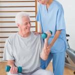 Senior man training with his therapist in fitness studio