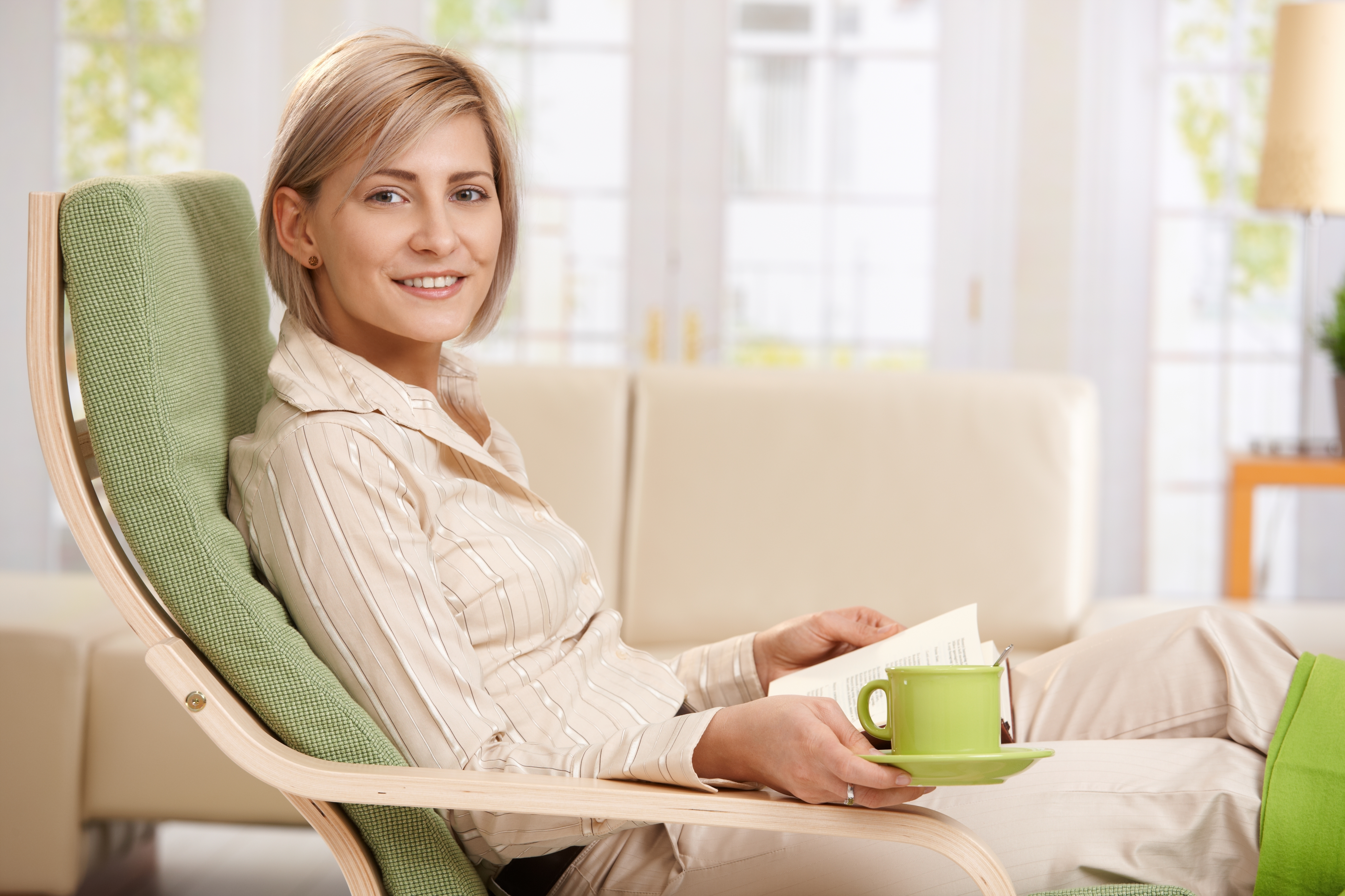 Woman relaxing in armchair at home, reading book , holding coffe